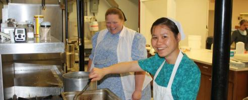Nueng Nuengruethai, international student from Thailand, helps Beatrice King prepare an authentic Thai meal